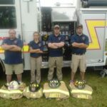 Fire Department Staff Standing by Truck and Gear